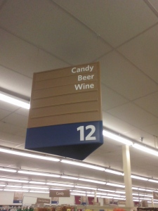 "grocery store aisle sign reading ""Candy, Beer, Wine"""